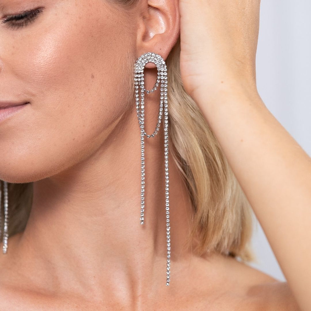 Girl wearing Product photo of oversized, statement drop earrings embellished with clear mineral zircon crystals.