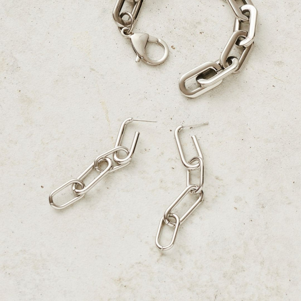 Flatlay of Stainless steel, chain drop earrings with four loops in silver styled next to chunky chain bracelet in silver.