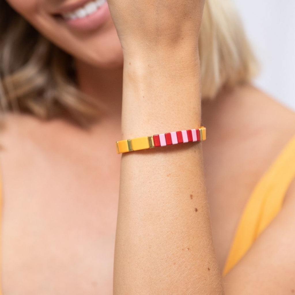 Girl wears elasticised bracelet made of squared metal beads with coloured (orange, pink, red and gold) enamel coating.