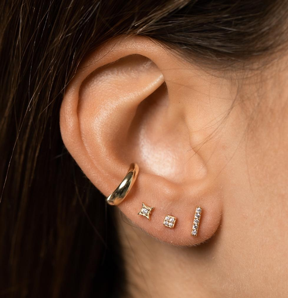 Photo of girl's ear with three small diamante studs and one 3mm gold plated, sterling silver ear cuff worn on conch.