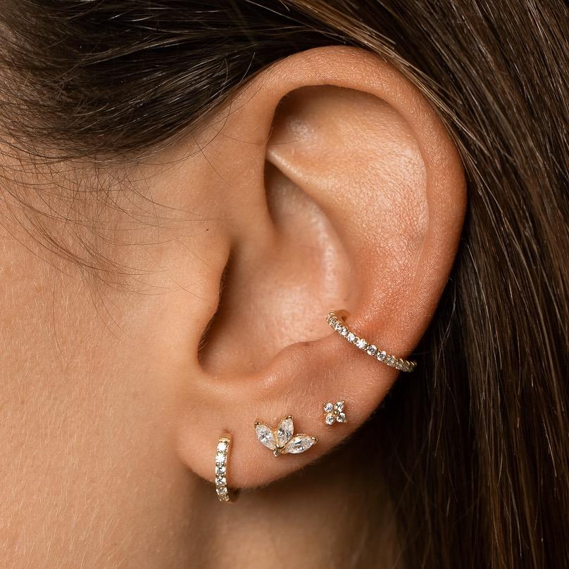 Closeup of girl's ear with gold version of Sterling silver ear cuff with zircon mineral stones  worn on the conch and stack of three studs in the lobe.