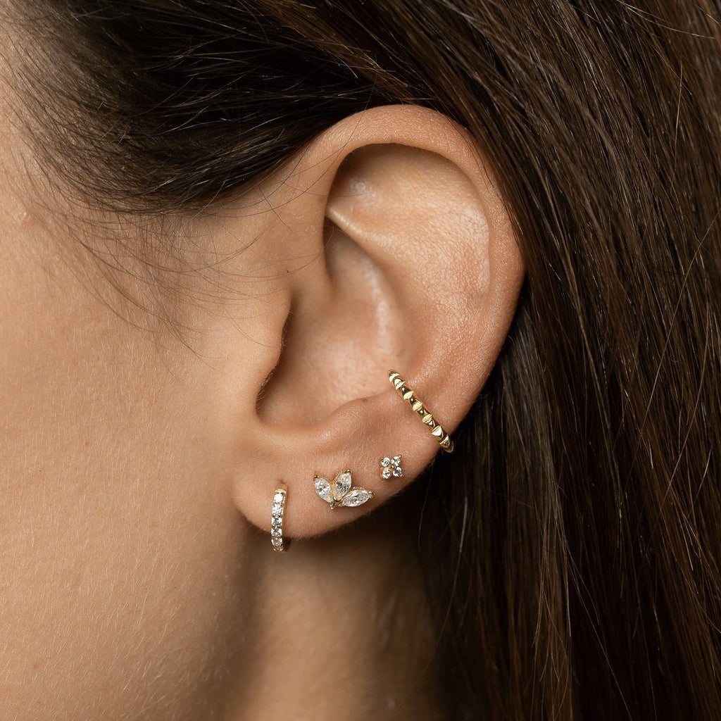 Closeup of girl's ear with  gold plated sterling silver ear cuff with zig zag detail worn at the conch above stack of three, mixed studs.