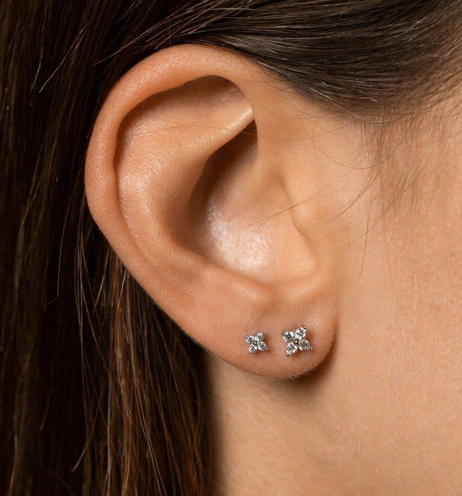 Closeup of girl's ear with 4mm sterling silver studs with four zircon mineral stones in flower shape worn in second lobe piercing and bigger version of same product in the first lobe piercing.