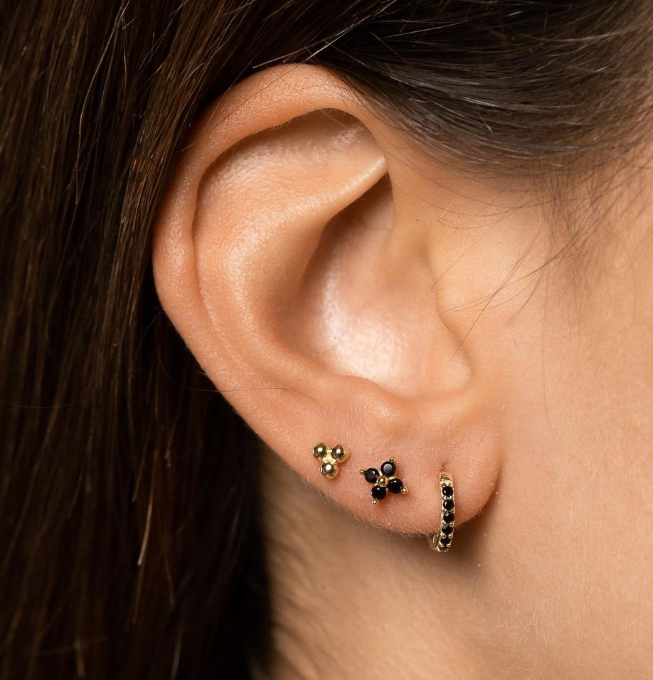 Closeup of girl's ear stick featuring mixed, gold and black huggies and studs.