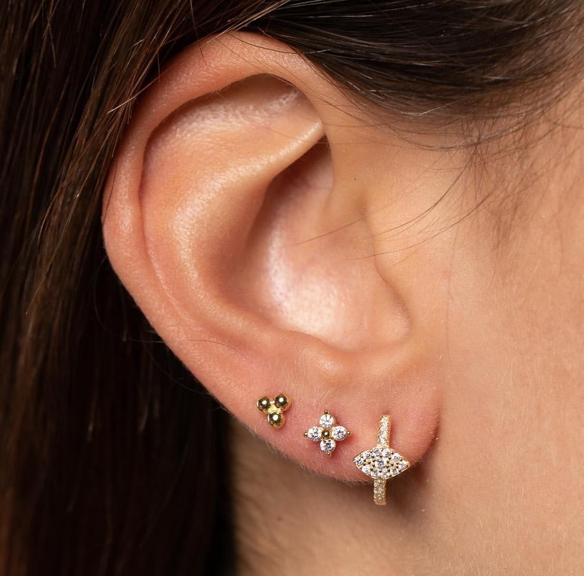 Closeup of girl's ear with mixed earring ear stack.