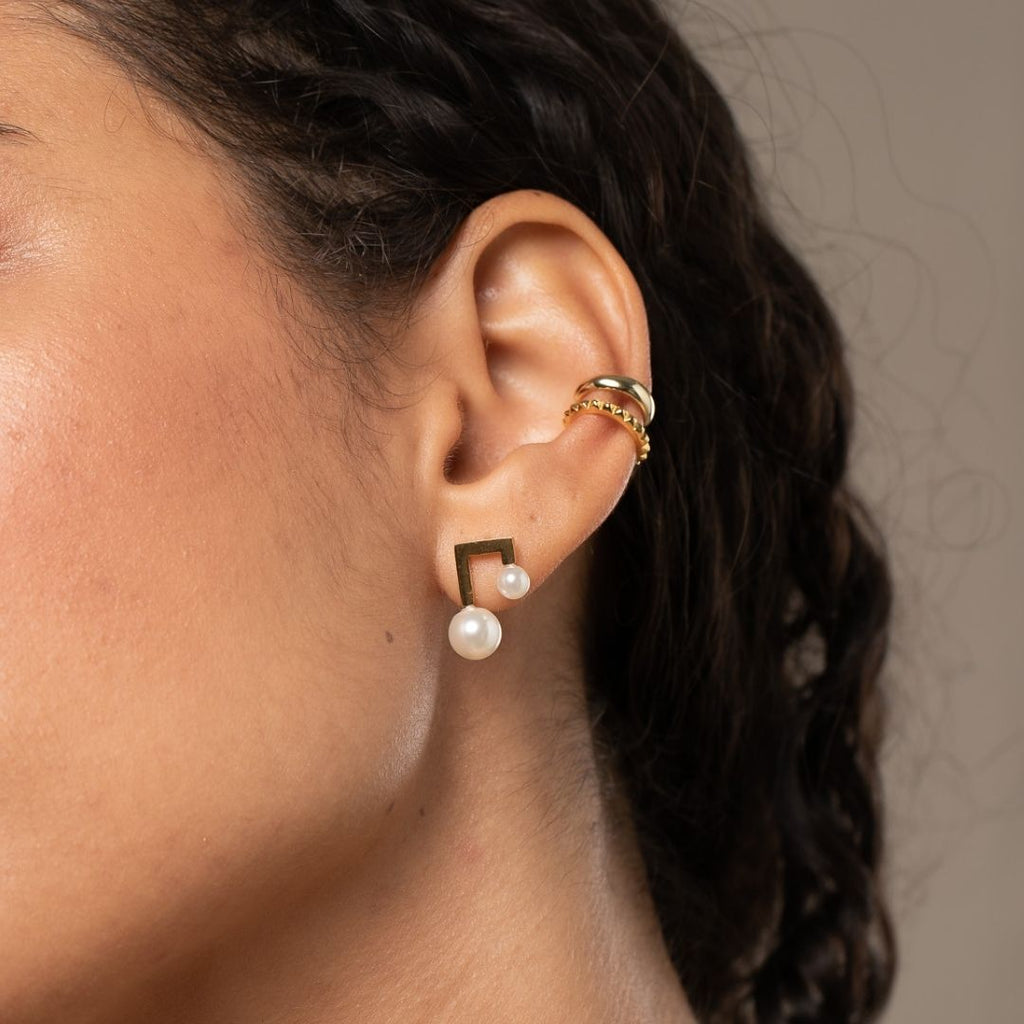 Closeup of girl's ear with Gold plated stud earrings featuring two imitation pearls worn in first lobe piercing.