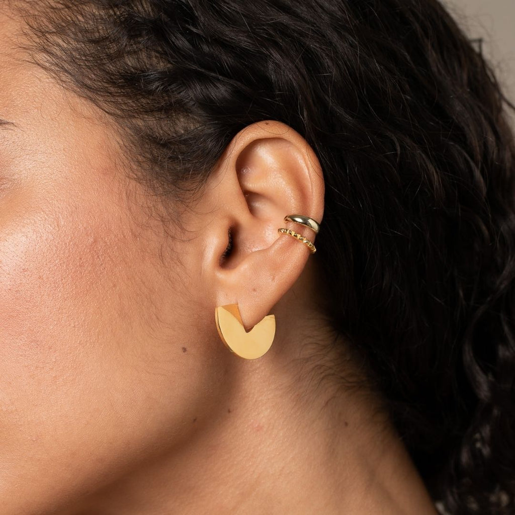 Closeup photo of girl's ear wearing Gold plated, sterling silver disc shaped hoop in first lobe piercing.