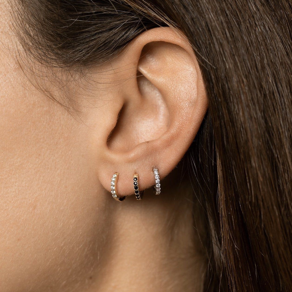 Close up of girl's ear with three huggies in ear stack.
