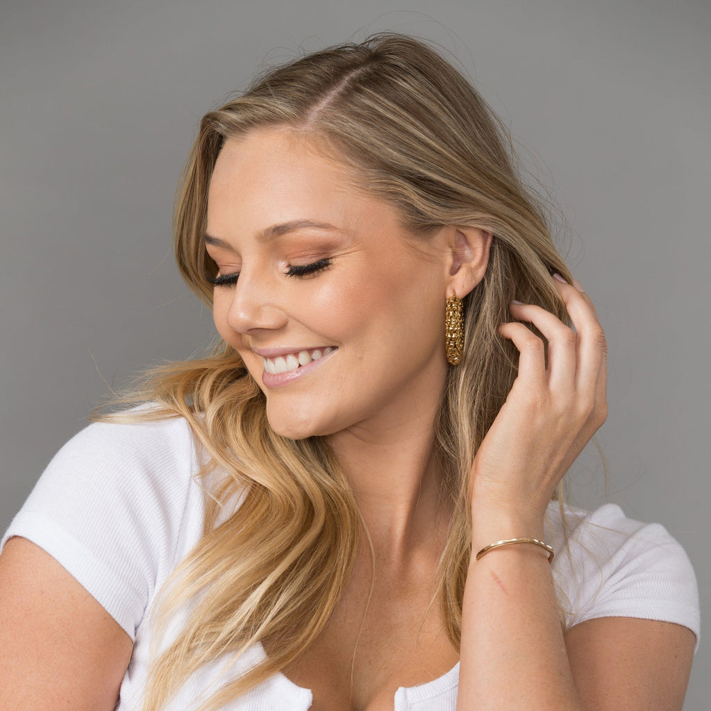 Portrait photo of girl wearing gold-plated popcorn chain hoops.