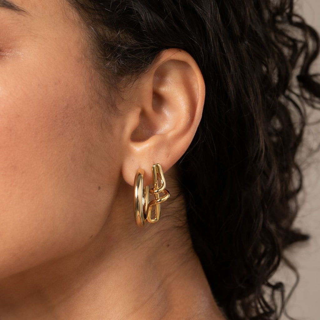 Girl wears gold plated, round shaped hoop earrings, and twirly gold studs.