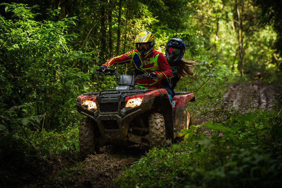 A man and woman riding an ATV down a trail