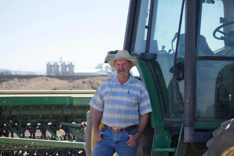 Brad Klann farms owner of Brad Klann Farms and Mecca Grade Estate Malt in central Oregon standing in front of a John Deer tractor, overlooking their farm and the Deschutes River Canyon.