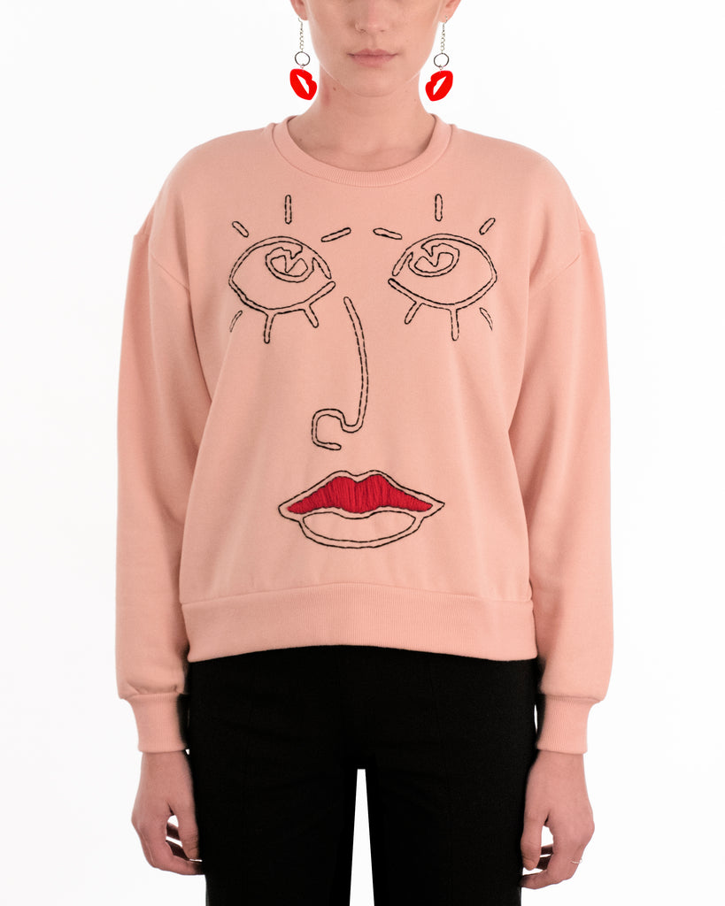 west carolina barcelona jumper in pink with black red hand stitched embroidery of a face red lips eyes
