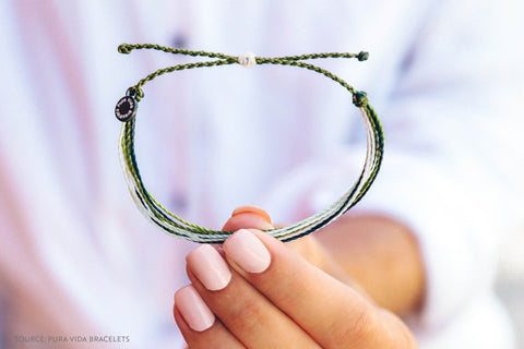 Pura Vida Bracelets Model Holding a Grey Charity Bracelet - Connected Clothing Company Blog - 7 Eco-friendly Companies That Give Back To The Planet