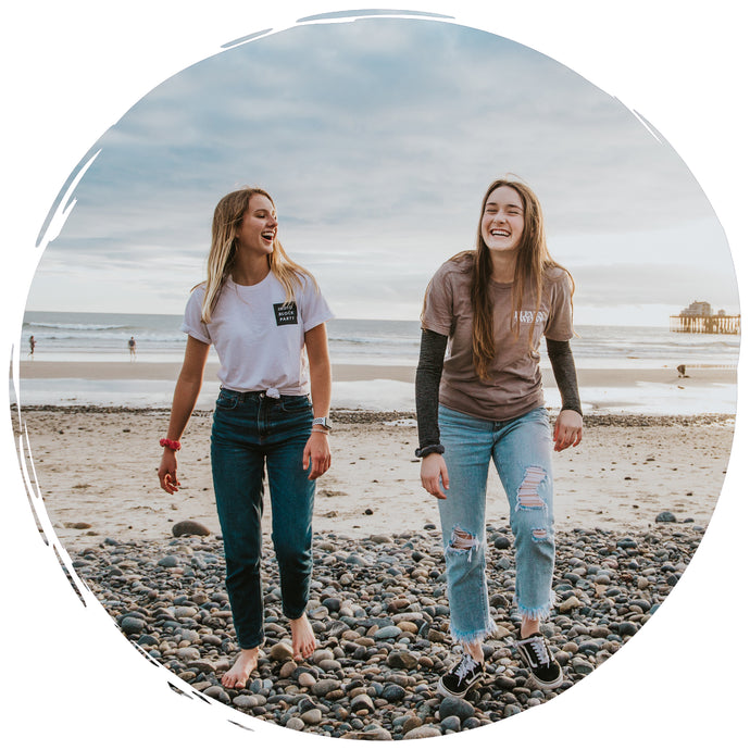 two friends laughing while walking on a beach - Connected Clothing Company Brand Ambassador Program