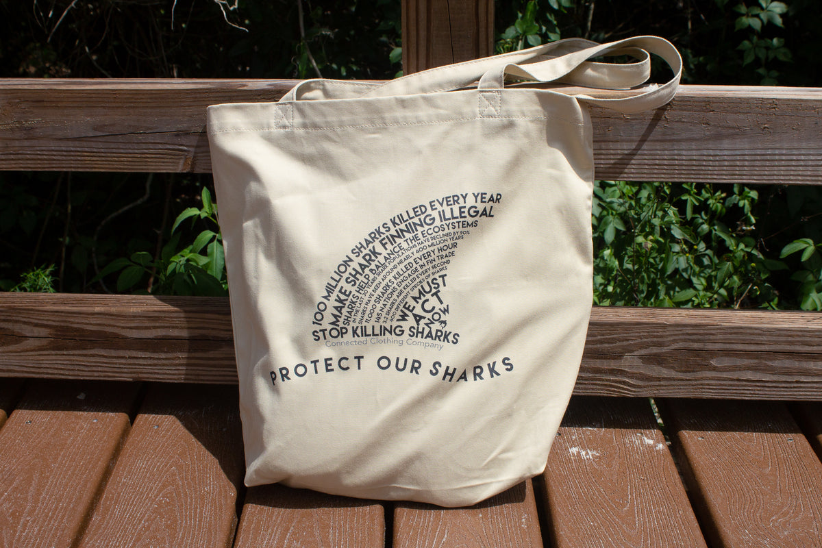 beige colored Protect Our Sharks Eco Tote sitting on beach boardwalk - Connected Clothing Company - 10% of profits donated to shark conservation efforts