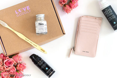 Love Goodly Box with Items Surrounding It, Bamboo Toothbrush, Vegan Leather Wallet, and Face Products - Connected Clothing Company Blog - 7 Eco-friendly Companies That Give Back To Our Planet