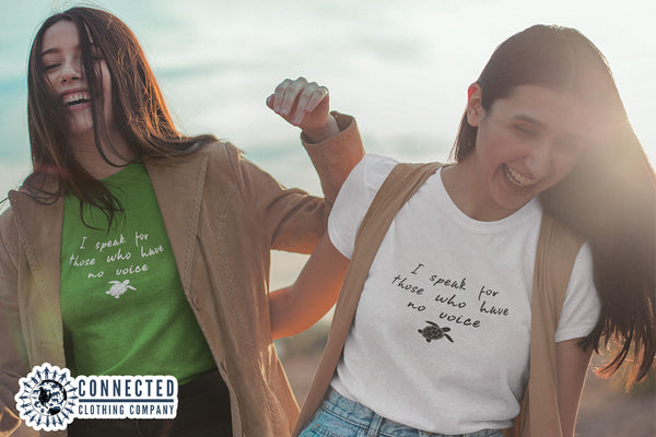Friends laughing while wearing green and white Be The Voice Sea Turtle Short-Sleeve Tees on the beach Connected Clothing Company - Ethically and Sustainably Made - 10% donated to the Sea Turtle Conservancy