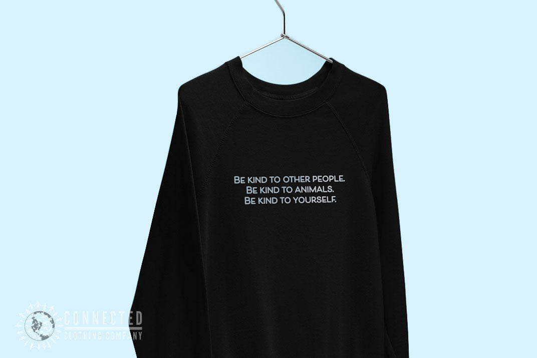 Be Kind To All Sweatshirt hanging in front of a blue background