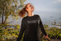 smiling model wearing black Be Kind To All Sweatshirt near the water