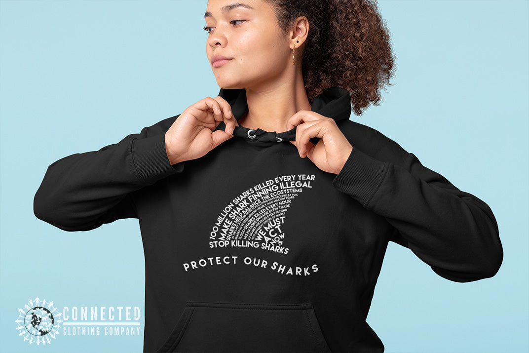 Model wearing black Protect Our Sharks Unisex Hoodie in front of blue backdrop - Connected Clothing Company - Ethically and Sustainably Made - 10% donated to Oceana shark conservation