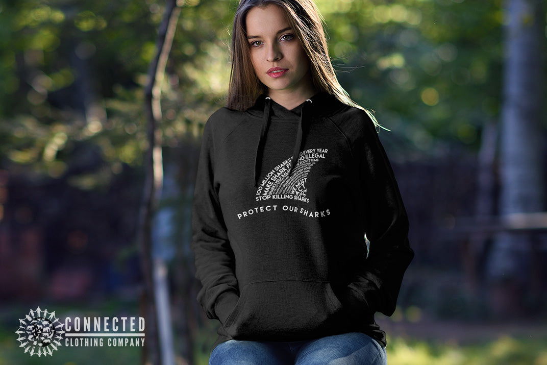 woman in forest wearing black Protect Our Sharks Unisex Hoodie - Connected Clothing Company - Ethically and Sustainably Made - 10% donated to Oceana shark conservation