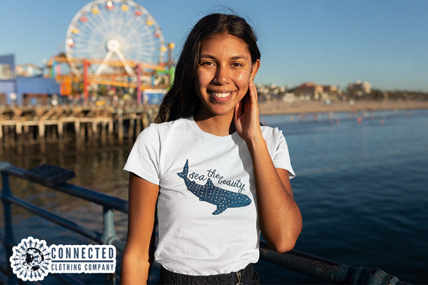Model wearing white Sea The Beauty Short-Sleeve Tee in front of ocean boardwalk - Connected Clothing Company - Ethically and Sustainably Made - 10% donated to Mission Blue ocean conservation