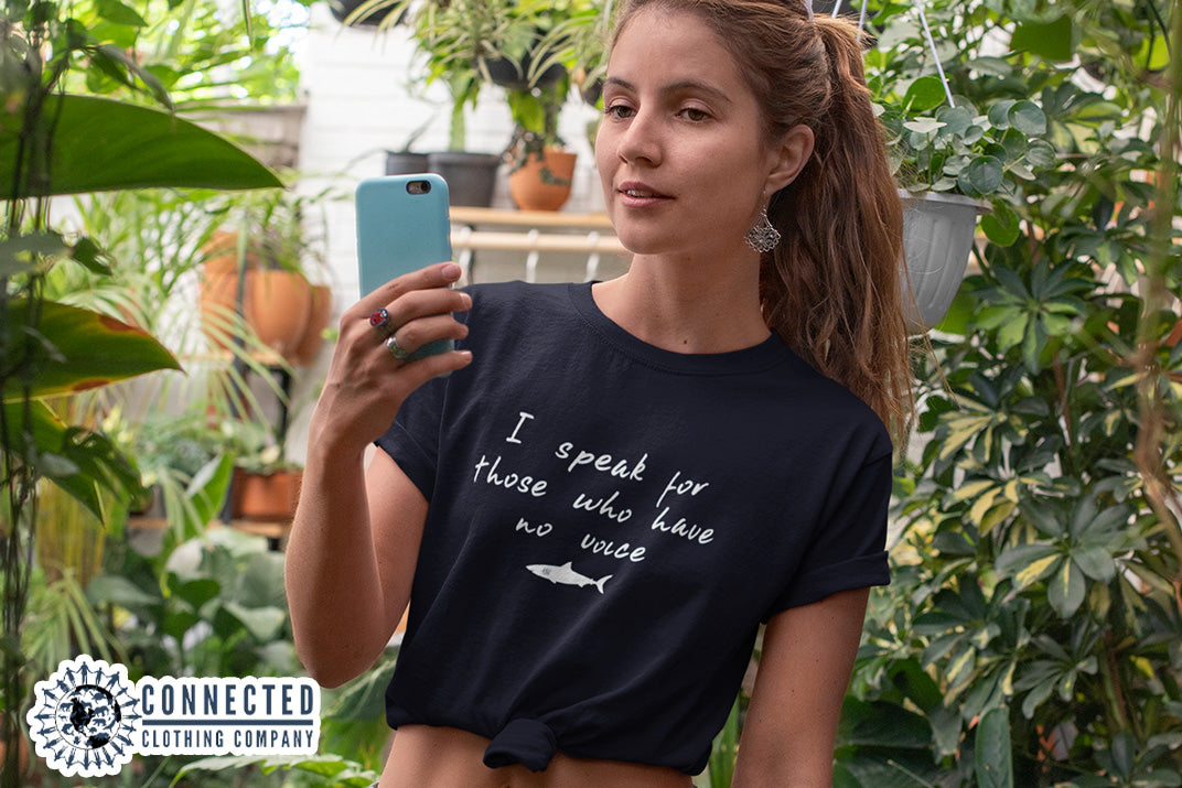 model wearing navy blue Be The Voice Shark Tee in a greenhouse - Connected Clothing Company - Ethically and Sustainably Made - 10% donated to Oceana shark conservation