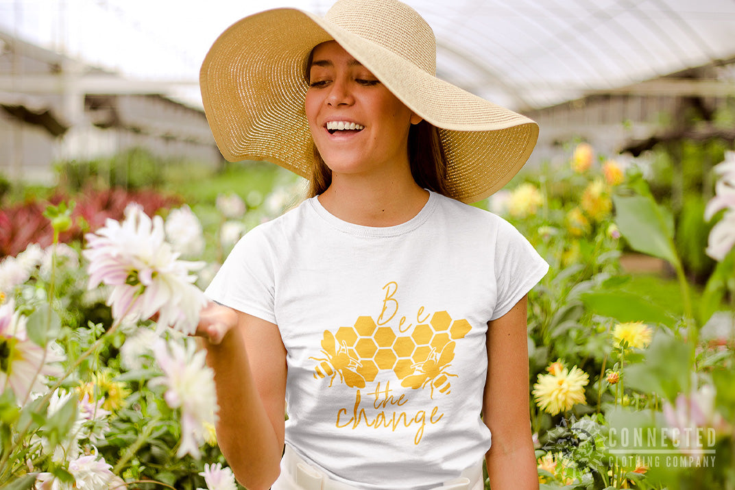 woman in a greenhouse wearing white Bee The Change Tee while smiling and smelling a flower