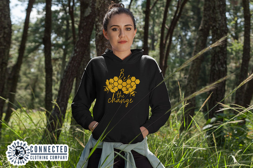 Model Wearing Black Bee The Change Hoodie In A Field - Ethically & Sustainably Made - Connected Clothing Company - 10% donated to The Honeybee Conservancy