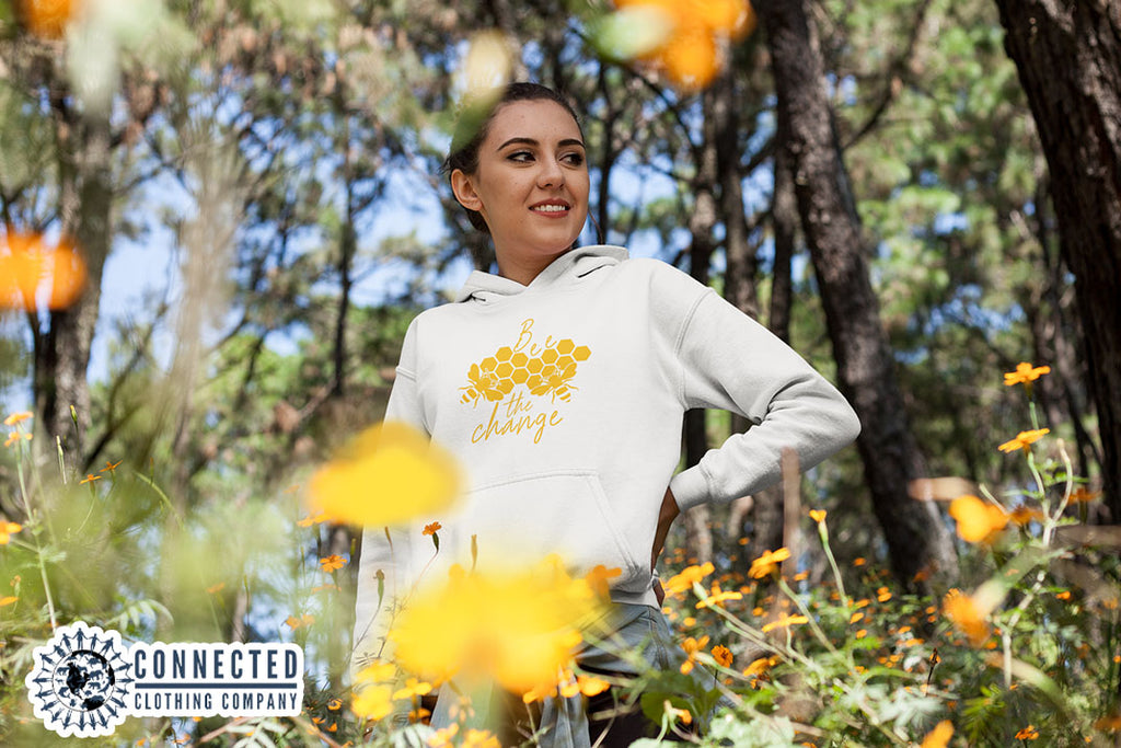 Model Wearing White Bee The Change Hoodie In A Field - Ethically & Sustainably Made - Connected Clothing Company - 10% donated to The Honeybee Conservancy