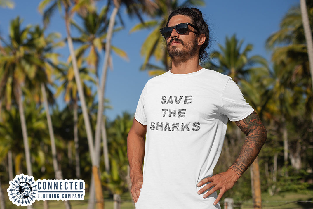 "Male Model Wearing White Save The Sharks Short-Sleeve Unisex T-Shirt reads ""Save The Sharks."" - Connected Clothing Company - Ethically and Sustainably Made - 10% donated to Oceana shark conservation"