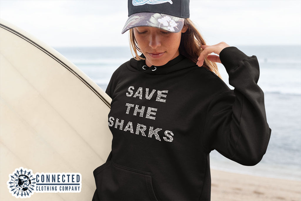 woman on the beach wearing black Save The Sharks Unisex Hoodie - Connected Clothing Company - Ethically and Sustainably Made - 10% donated to Oceana shark conservation