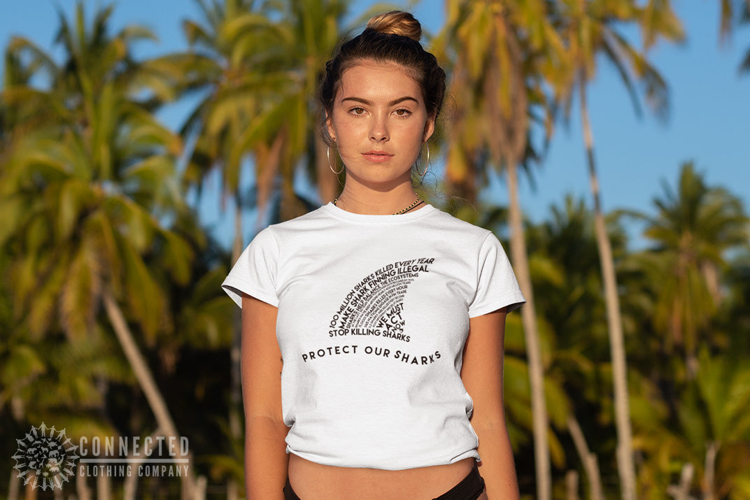 Woman on beach with palm trees in the background wearing Connected Clothing Company Protect Our Sharks Tee in White