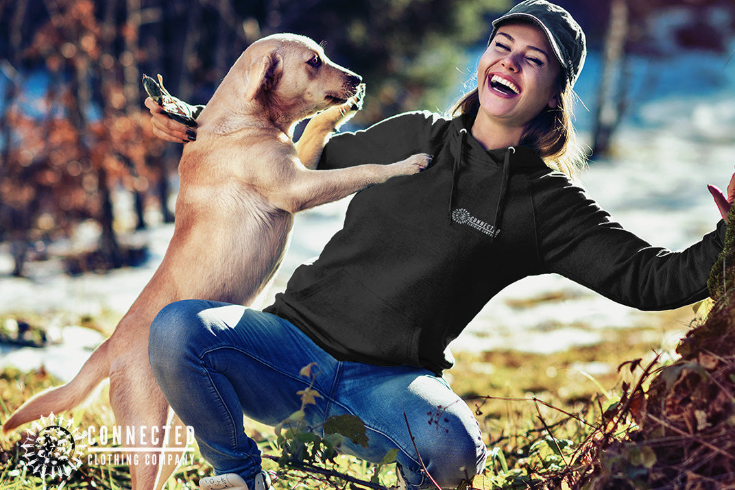Model wearing Black Show Humanity Unisex Hoodie while smiling and playing with a rescue dog - Connected Clothing Company - Ethically and Sustainably Made - 10% donated to the Society for the Prevention of Cruelty to Animals