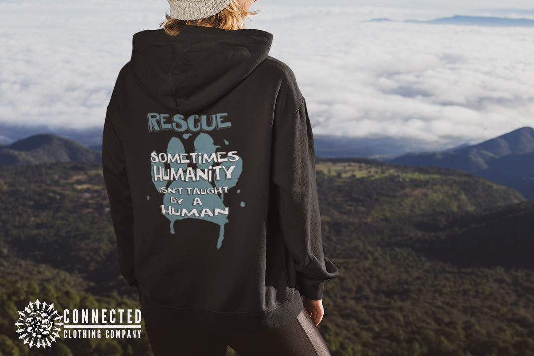 """Model wearing Black Show Humanity Unisex Hoodie at the mountains that reads """"Rescue. Sometimes humanity isn't taught by a human"""" - Connected Clothing Company - Ethically and Sustainably Made - 10% donated to the Society for the Prevention of Cruelty to Animals"""