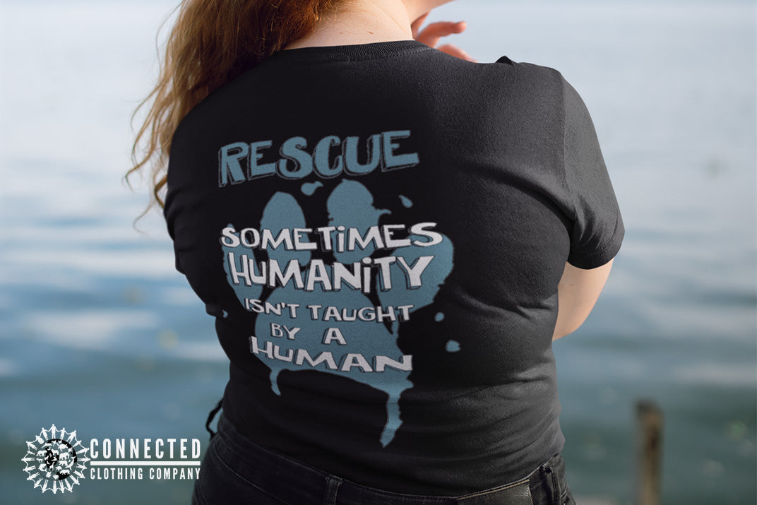 "Model wearing Black Show Humanity Tee at the lake that reads ""Rescue. Sometimes humanity isn't taught by a human"" - Connected Clothing Company - Ethically and Sustainably Made - 10% donated to the Society for the Prevention of Cruelty to Animals"