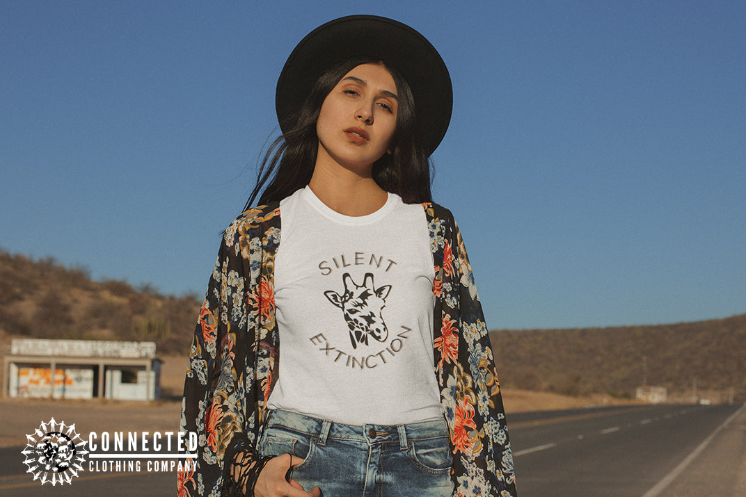 Model woman in the desert wearing white Giraffe Silent Extinction Short-Sleeve Tee - Connected Clothing Company - Ethically and Sustainably Made - 10% donated to Giraffe Conservation Foundation