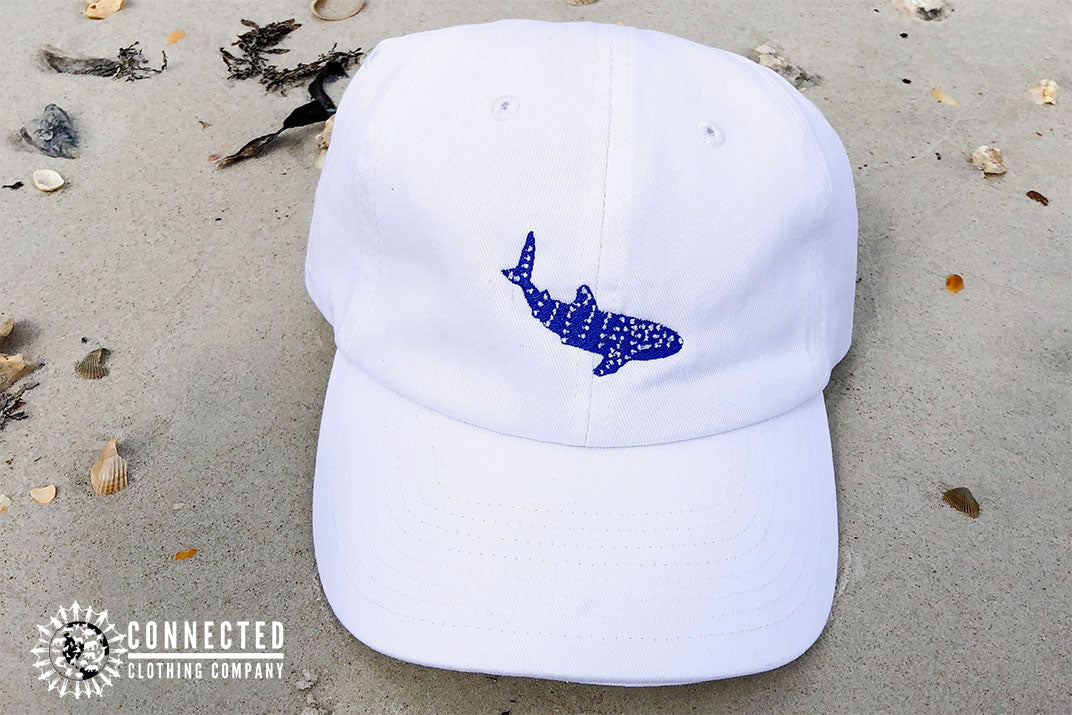 White Whale Shark Cotton Cap on beach sand - Connected Clothing Company - Ethically and Sustainably Made - 10% donated to Mission Blue ocean conservation
