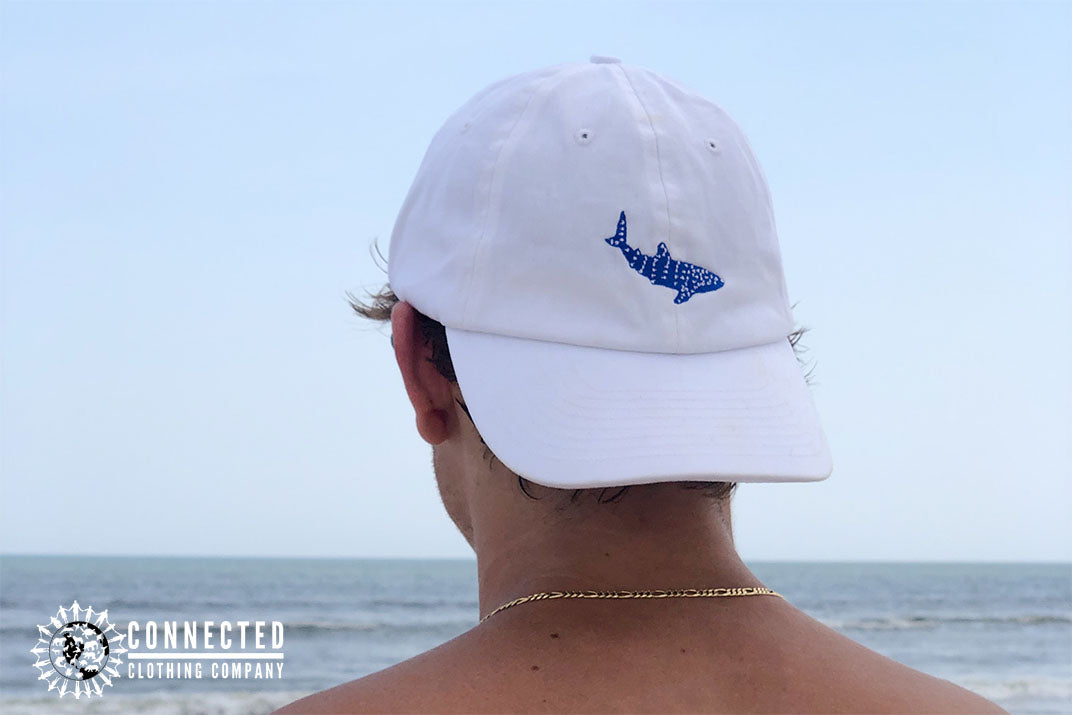 man on the beach wearing white Whale Shark Cotton Cap - - Connected Clothing Company - Ethically and Sustainably Made - 10% donated to Mission Blue ocean conservation