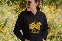 model wearing black Bee The Change Unisex Hoodie in field of flowers - Connected Clothing Company - 10% of profits donated to bee conservation efforts