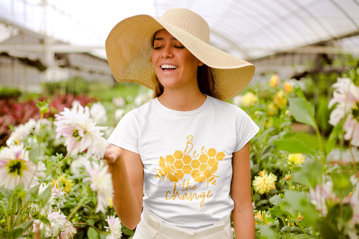 Model wearing white Bee The Change Short-Sleeve Tee in garden - Connected Clothing Company - 10% of profits donated to save the bees