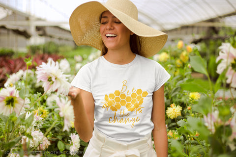 Model Wearing Connected Clothing Company Bee The Change T-shirt in a greenhouse surrounded by flowers- Connected Clothing Company Blog - 7 Eco-friendly Companies That Give Back To Our Planet