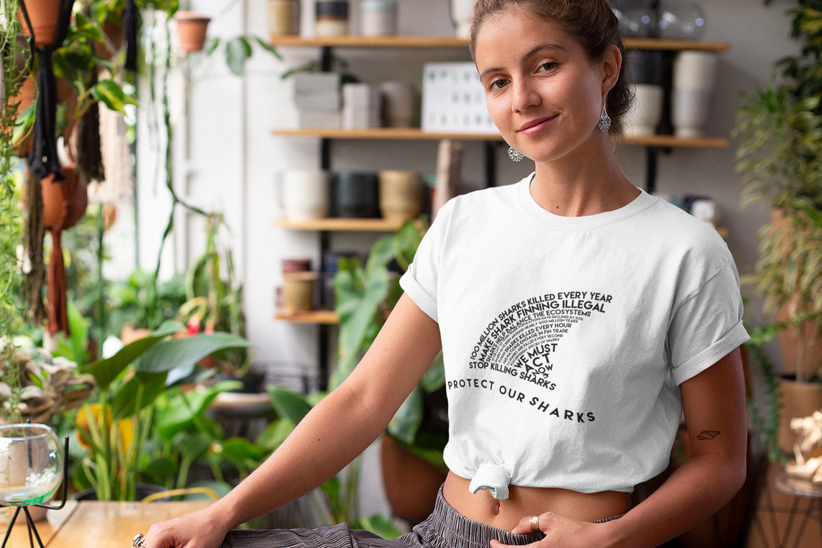 model wearing white Organic Protect Our Sharks Short-Sleeve Tee surrounded by plants - Connected Clothing Company - 10% of profits donated to shark conservation