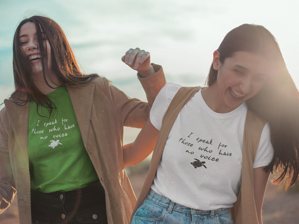 "Models wearing green and white Be The Voice Sea Turtle Short-Sleeve Tees while laughing on the beach. Shirt reads ""I speak for those who have no voice""."
