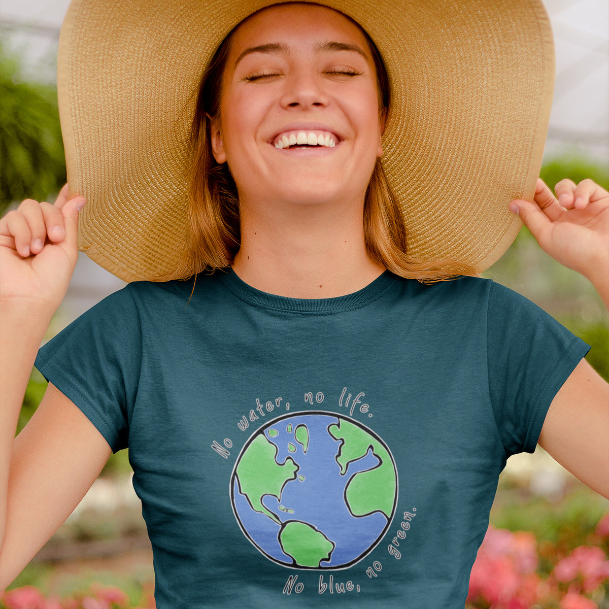 "girl in greenhouse with flowers and sunhat wearing Connected Clothing Company ""No Blue No Green"" tshirt - 10% of profits give back to non-profit organizations - ethically and sustainably made clothing"