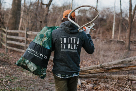 United By Blue Team Member Wearing a Jacket and Carrying a Bag of Trash During a Cleanup - Connected Clothing Company Blog - 7 Eco-friendly Companies That Give Back To Our Planet