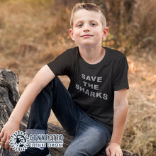 Load image into Gallery viewer, Boy Model Wearing Black Save The Sharks Youth Short-Sleeve Tee - Connected Clothing Company - 10% of profits donated to Oceana shark conservation