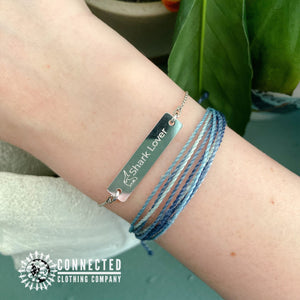 White Rhodium Coated Shark Lover Engraved Bar Chain Bracelet on arm (shark icon with shark lover written on a bracelet) - Connected Clothing Company - 10% of profits donated to Oceana shark conservation