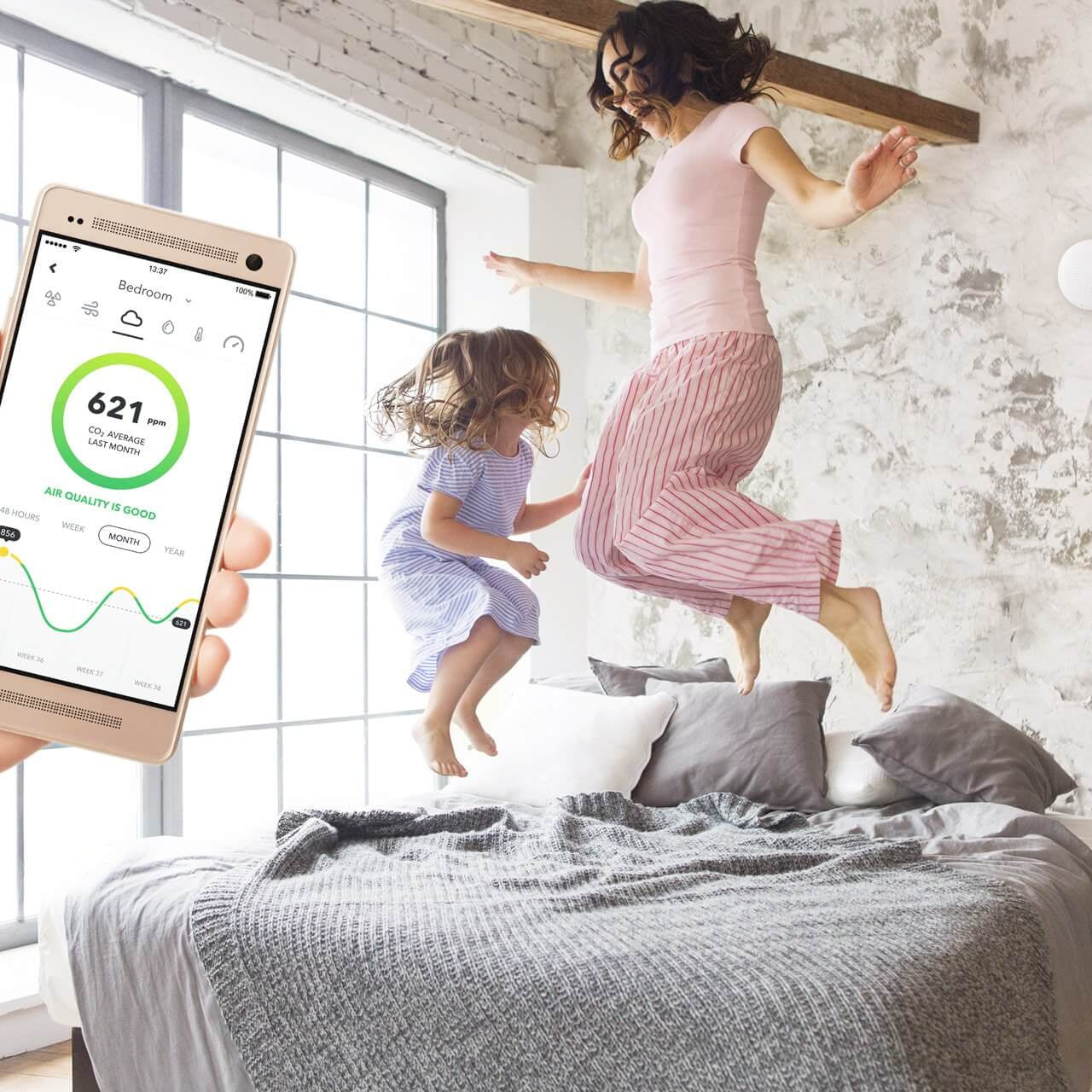 Air quality monitor and happy family breathing fresh air